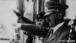 Adolf Hitler and Benito Mussolini give the fascist salute at a parade during 1943