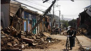 Man pushes his bicycle past ruined buildings in Talca Chile