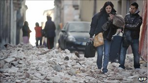 People walk on rubble in the centre of L'Aquila (April 6, 2009)