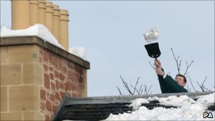 A man uses a shovel to remove snow from the roof of a house in Edinbu