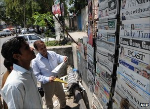 Pakistani men at newsstands in Islamabad
