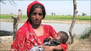 Woman with her baby surrounded by flood waters, Sindh province