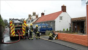 Guernsey fire engine and firefighters damping down shed fire