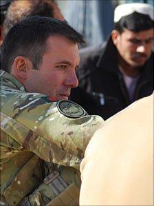 Major Mark Beynon drinks chai with village elders at a shura