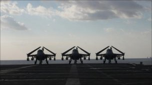 Three planes sitting by the runway on the USS George Washington