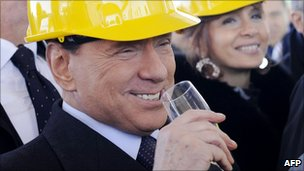 Italian Premier Silvio Berlusconi, wearing a worker's helmet, toasts during the inauguration of work on a new hall for high speed trains at Rome's Tiburtina train station, 10 December 2010