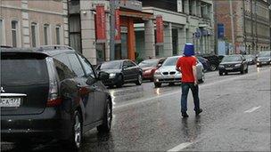 Voina president Leonid Nikolayev walks down the street with a blue bucket on his head