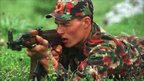 A Kosovo Liberation Army fighter aims his AK-47 in a training camp in northern Albania, May 1999