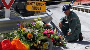 A miner lays down flowers at White Knight Bridge near the entrance to the Pike River mine where 29 miners died, in Greymouth