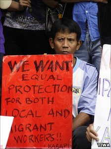 A migrant worker holds a sign calling for equal rights (Photography by Jung-Lung Chang, provide by TIWA)