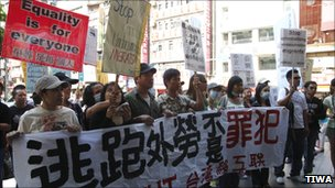 Migrant workers hold sign calling for minimum wage (Photography by Jung-Lung Chang, provide by TIWA)
