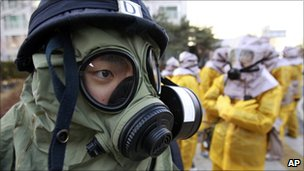 South Korean police and civilians wear gas masks during a civil defence drill