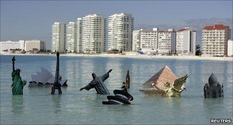 Models of world landmarks in the sea off Cancun placed there by demonstrators