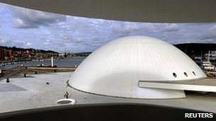 White dome of Niemeyer Centre in Aviles, Spain, with port in the background