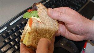 Man holding sandwich over computer keyboard