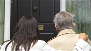 Two people by a front door