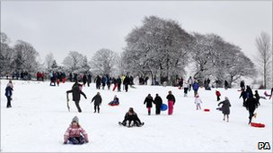 People sledging in the snow