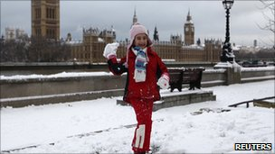 A young girl throws a snowball while  opposite the Houses of Parliament