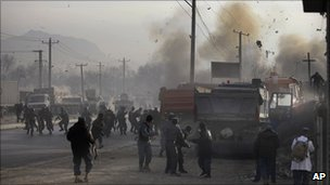 Afghan soldiers run for cover as a bomb explodes during a gun battle on the outskirts of Kabul, Afghanistan, on Sunday