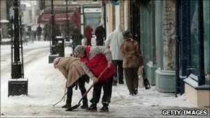Shopkeepers try to clear snow