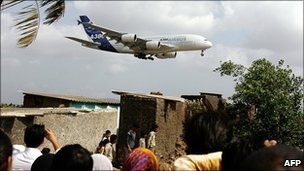 Indian onlookers watch as a superjumbo prepares to land at Mumbai's existing airport