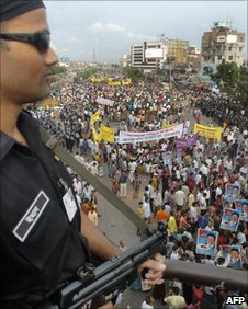 A Bangladesh Rapid Action Battalion officer watches an opposition rally in Dhaka in July 2006