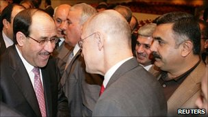 Prime Minister Nouri Maliki (L) is congratulated after forming the new government at the parliament in Baghdad