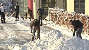 Men shovelling snow in a street