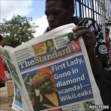 A man reads a copy of the Independent Standard newspaper on the streets of Harare, 13 December 2010