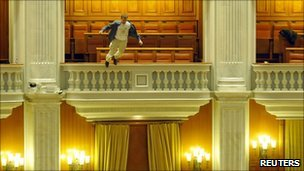 Protestor Adrian Sobaru jumps from a balcony in the Romanian parliament