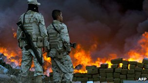 Two soldiers watch 134 tonnes of marijuana burning on October 20