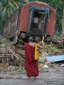 Buddhist monk looks at a wrecked train carriage 30 December 2004 near Galle, Sri Lanka