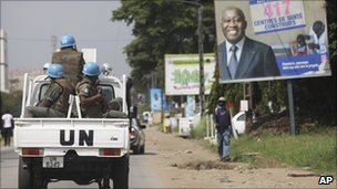 UN peacekeepers drive past a poster for Laurent Gbagbo on a street in Abidjan (23 December 2010)