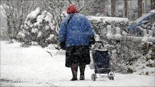 A woman drags a shopping trolley through snow