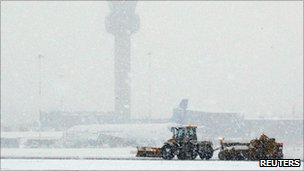 Snow ploughs clear a runway