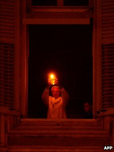 The Pope lights a nativity candle from his window