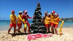 Life guards with a Christmas tree on Bondi Beach