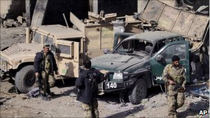 Policemen stand near vehicles damaged in Monday's bomb attack