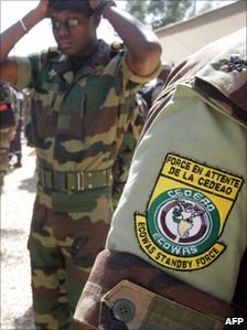 An officer from the West African standby force his cap during exercises during military manoeuvres in Senegal