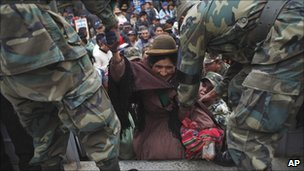 Soldiers help a woman on to a military truck during the strike in El Alto, Bolivia