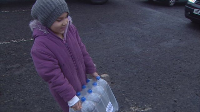 Girl carrying bottles of water