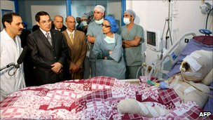 A handout picture released by the Tunisian Presidency on 28 December 2010 shows Tunisian President  Zine al-Abidine Ben Ali (2nd L) looking at Mohammed Bouazizi(R), during his visit at the hospital