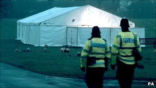 Police officers walk by a tent set up to exhume the remains of James Hanratty at Carpenders Park cemetery in Bushey, Hertfordshire