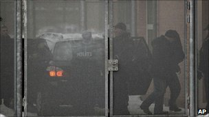 Danish police officers escort one of four suspects, (second from right), arrested on suspicion of planning a shooting attack on the office of a newspaper that published cartoons of the Prophet Muhammad, at a court in Glostrup, west of Copenhagen, 30 December 2010