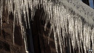 Icicles hang down from a gutter