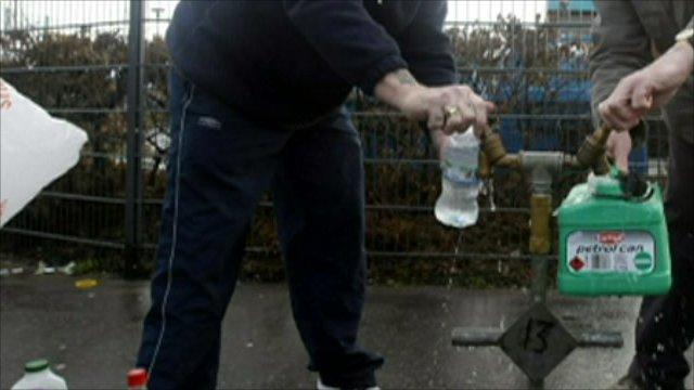People filling water bottles