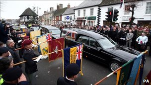 Mourners watch the hearse carrying Cpl Steven Dunn's coffin