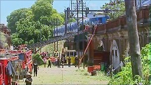 Fire engines stand below the Buenos Aires rail bridge on which a damaged train stands, 31 December