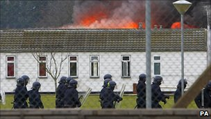 Specialist prison officers in riot gear in front of one of Ford's burning buildings