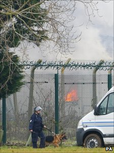 A prison officer patrols the Ford perimeter fence